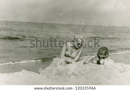 Vintage photo of mother and daughter playing on beach (fifties) - stock photo