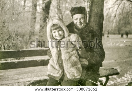 Vintage photo of mother and daughter sitting on bench in winter, 1950's - stock photo