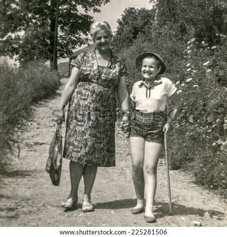 Vintage photo of mother and daughter walking outdoor, sixties - stock photo