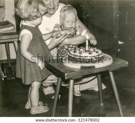 Vintage photo of mother and little children - first birthday of baby boy - 1983 - stock photo