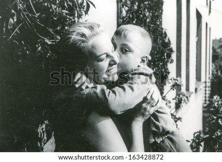 Vintage photo of mother and son on balcony, fifties - stock photo