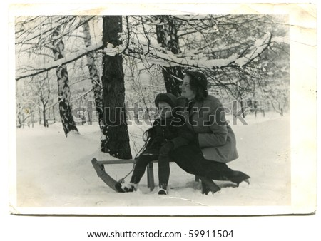 Vintage photo of mother and son on sled (early fifties) - stock photo