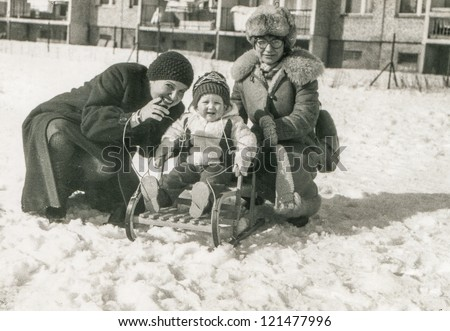 Vintage photo of mother, aunt and little girl on sled (early eighties) - stock photo