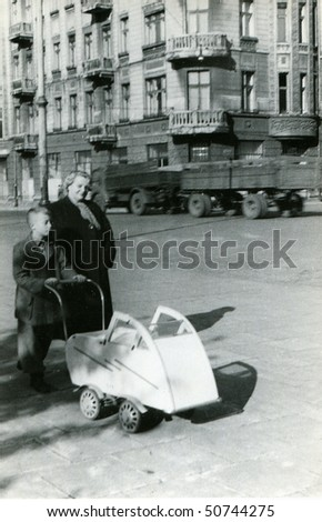Vintage photo of mother with a son and a baby in pushchair (1954) - stock photo