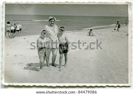 Vintage photo of mother with sons on beach (fifties) - stock photo