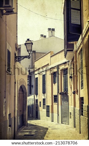Vintage photo of narrow street in old city of Palma de Mallorca, Spain - stock photo