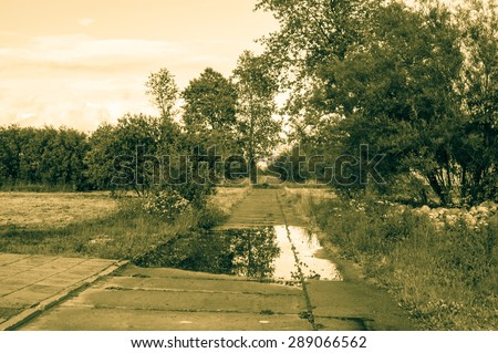 Vintage photo of nature landscape. Landscape with rural road, trees and puddle of rain at summer. Idyllic rural landscape and agricultural, with vintage vignette effect. - stock photo