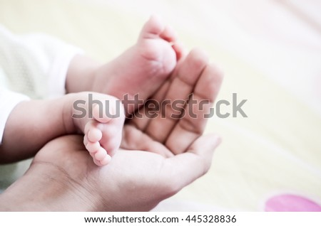 Vintage Photo of newborn baby feet on mother hand ( soft focus effect )
