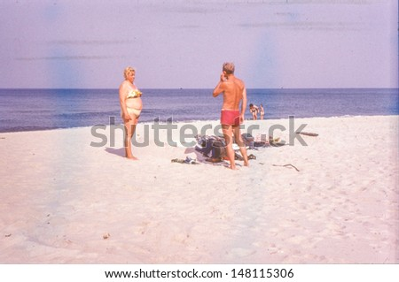 Vintage photo of overweight woman and her husband on beach , sixties - stock photo