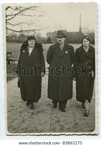 Vintage photo of  parents and daughter walking on the street (thirties) - stock photo