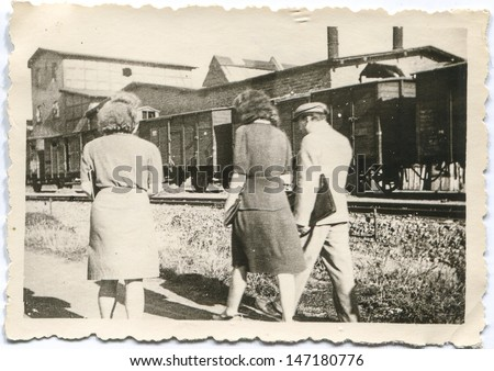 Vintage photo of people walking by railroad with a station and freight train in background, forties
