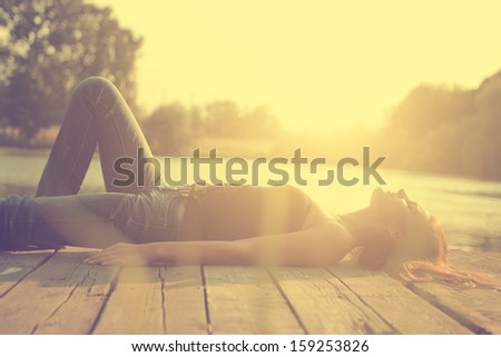 Vintage photo of relaxing young woman on wooden pier at the lake in sunset - stock photo