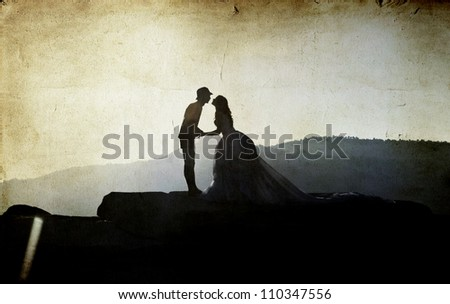 Vintage photo of silhouette image of a bride and groom - stock photo
