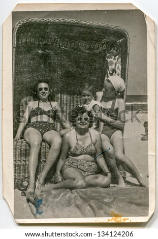 Vintage photo of three-generation family in beach basket, fifties - stock photo
