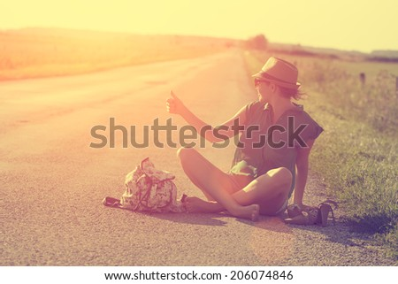 Vintage photo of traveler woman hitchhiking along lonely road in summer sunset - stock photo
