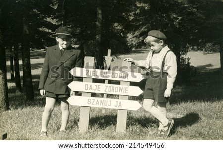 """Vintage photo of two brothers in park (inscription in Polish says: """"Green decorates and gives health, respect it"""" - stock photo"""