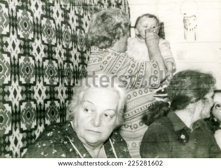 Vintage photo of two grandmothers, mother and baby girl during a family dinner, 1981 - stock photo
