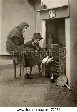 Vintage photo of two people warming feet at fireplace
