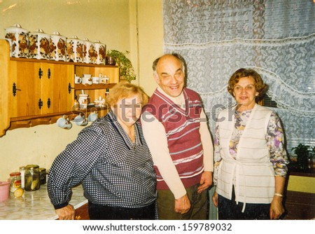 Vintage photo of two women and a man in kitchen, circa seventies - stock photo