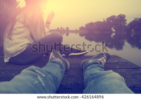 Vintage photo of woman and man relaxing on pier in sunset