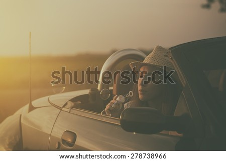Vintage photo of woman blowing soap bubbles from cabriolet car in sunset - stock photo