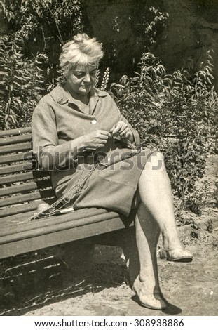 Vintage photo of woman knitting on bench, 1950's - stock photo
