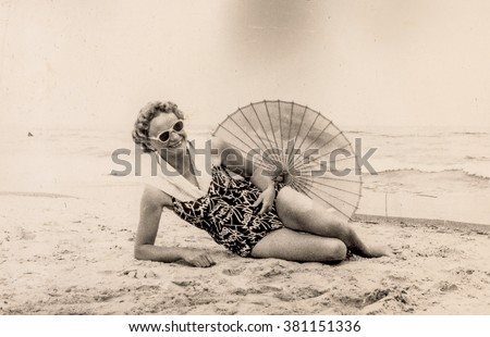 Vintage photo of woman resting on beach in swimsuit with umbrella (early 1960's) - stock photo