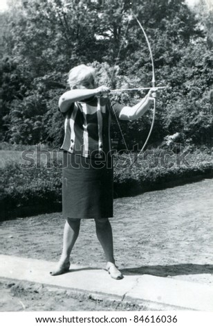 Vintage photo of woman  shooting a bow (fifties) - stock photo