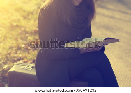 Vintage photo of woman with book on retro suitcase - stock photo