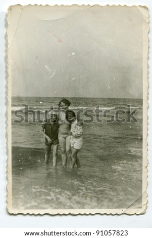 Vintage photo of woman with children on beach (fifties) - stock photo