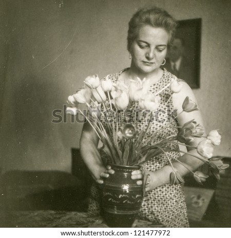 Vintage photo of woman with tulips (fifties) - stock photo