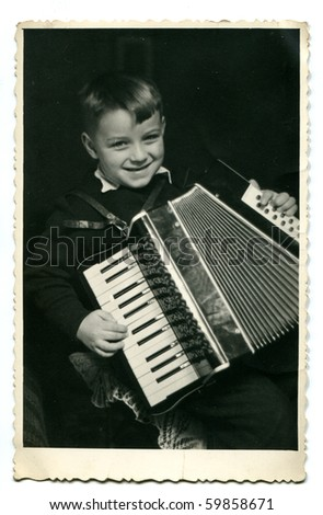 Vintage photo of young boy playing accordion - stock photo