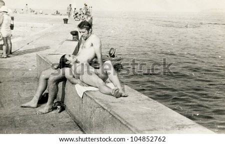 Vintage photo of young couple resting at seaside (seventies) - stock photo