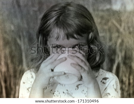 Vintage photo of young girl drinking from a mug (sixties) - stock photo