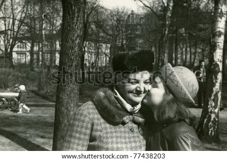 Vintage photo of young girl kissing her mother (early sixties) - stock photo