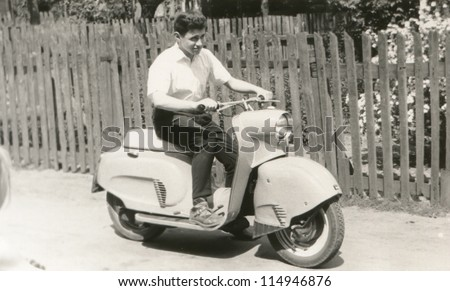 Vintage photo of young man on scooter (sixties) - stock photo