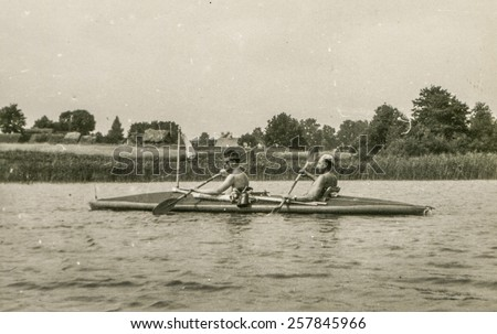 Vintage photo of young men during a canoe trip (1960's) - stock photo