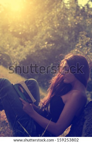 Vintage photo of young woman reading a book in park - stock photo