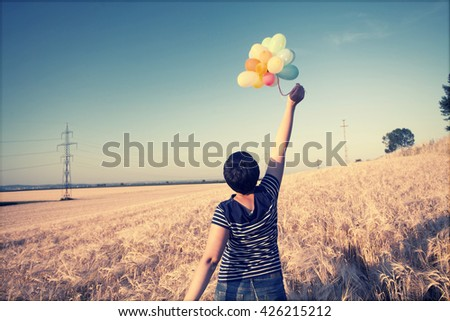 Vintage photo of young woman with colorful balloons in summer field