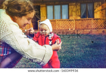 Vintage photo (scanned reversal film) - mother with baby daughter, early eighties - stock photo