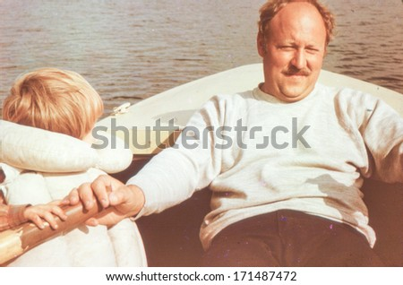 Vintage photo (scanned reversal film) of father with son on rowing boat (early eighties) - stock photo