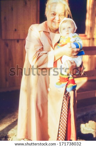 Vintage photo (scanned reversal film) of grandmother with a baby granddaughter, 1981  - stock photo