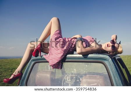 Vintage photo shoot. Girl in short dress teasing on car roof. - stock photo
