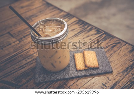 vintage photo style  classic tone of   fresh iced coffee and delicious cracker serve on stone tile tray - stock photo