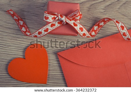 Vintage photo, Wrapped gift with ribbon, red wooden heart and love letter in envelope on wooden background, decoration for Valentines Day, copy space for text - stock photo
