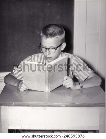 Vintage photograph of young boy reading a book at a desk in a school classroom - stock photo