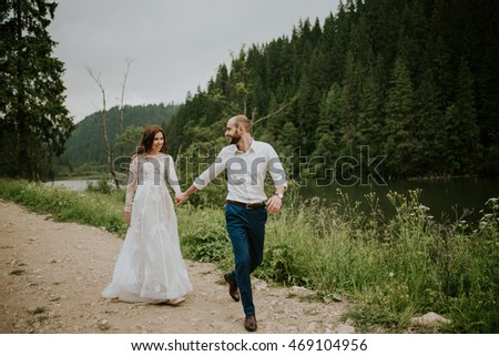 Vintage photography of a young hipster couple posing in wedding suite and dress at sunset in the forest and mountains