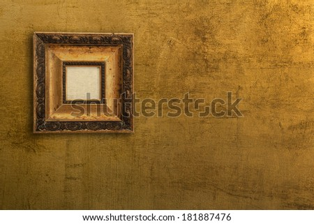 vintage picture frame on gold wall - stock photo
