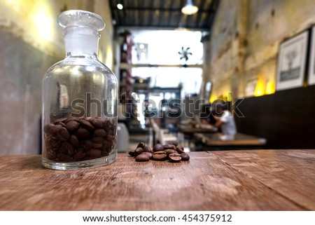 vintage picture tone Roasted brown coffee beans and A small glass jar on a wooden table with coffee cafe shop background