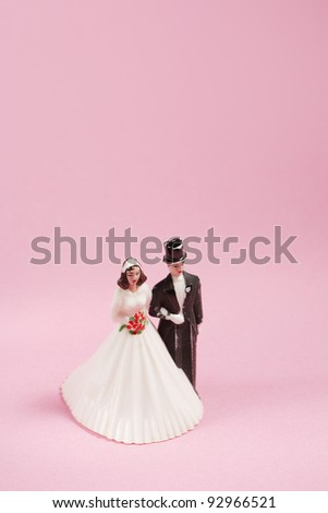 Vintage plastic wedding cake decoration on pink background. - stock photo
